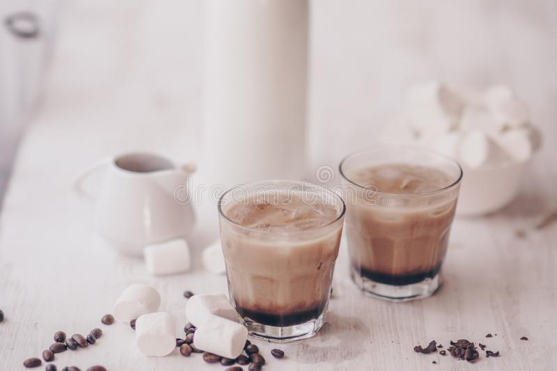 Summer drink. Cold coffee with milk and chocolate. Light background. Iced coffee. Marshmelow and coffee beans on the table. Concept of a cooling drink stock photos