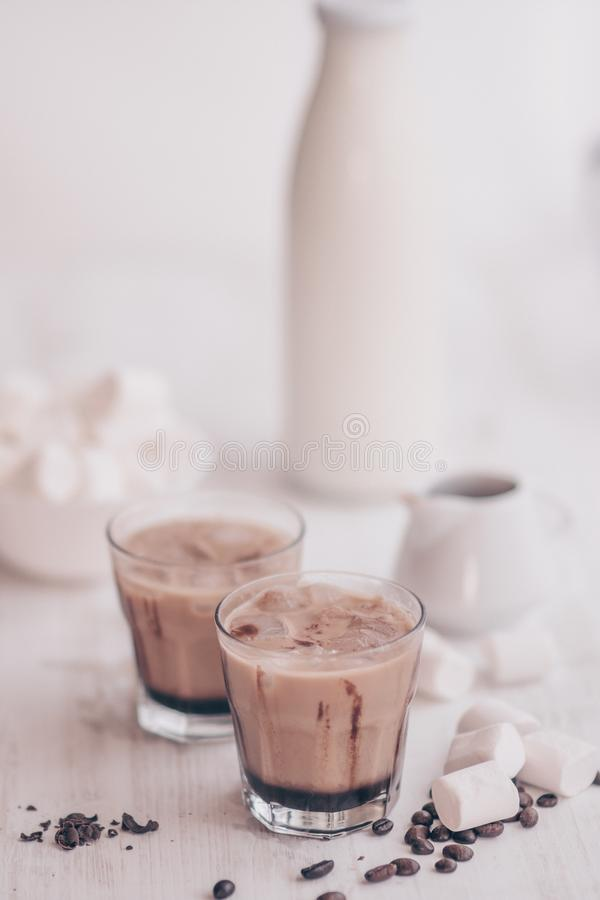 Summer drink. Cold coffee with milk and chocolate. Vertical shot. Light background. Iced coffee. Marshmelow and coffee beans on the table. Concept of a cooling royalty free stock images
