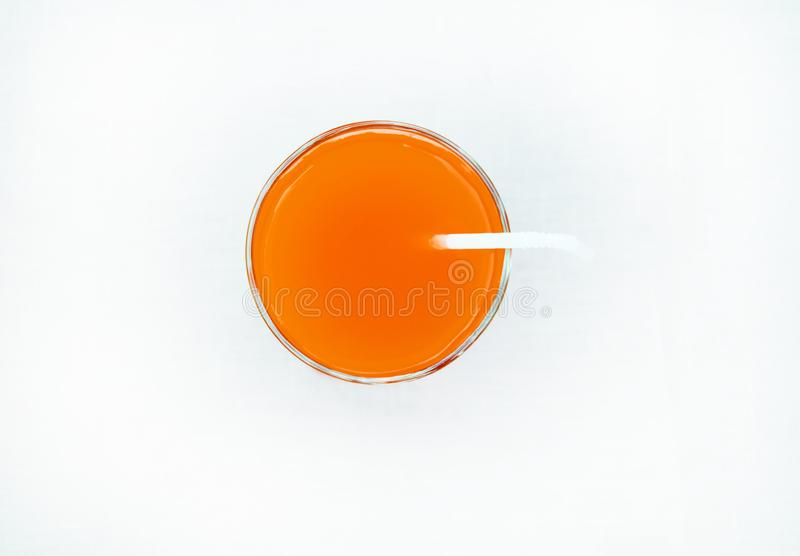 Summer drink - freshly squeezed grapefruit juice in a glass with a straw tube, top view, isolated on a white background with stock image