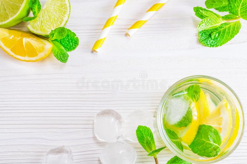 Summer drink mojito with lime, lemon and mint, with ice cubes on white wooden background. Flat-lay, top view. Glass with summer drink of lemon, lime and mint stock photography