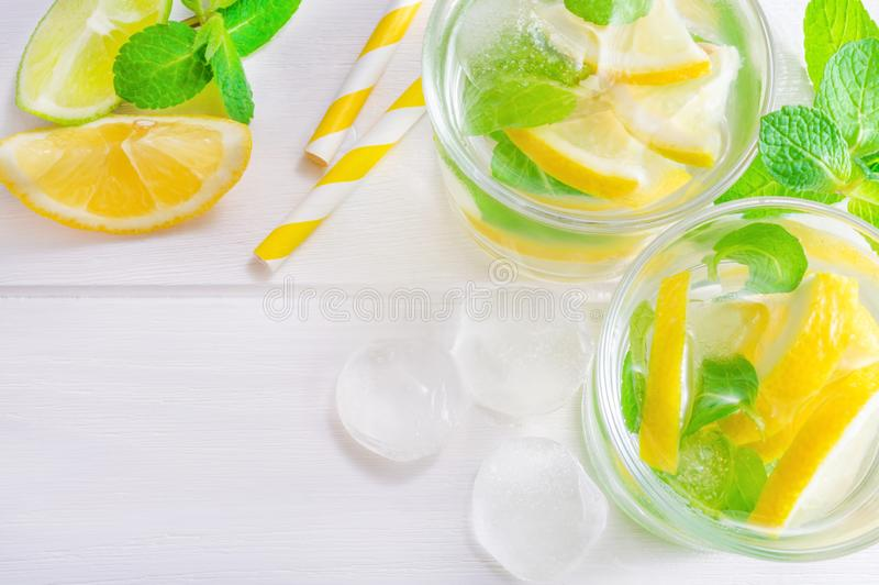 Summer drink mojito with lime, lemon and mint, with ice cubes on white wooden background. Flat-lay, top view. Two glasses with summer drink of lemon, lime and stock photo