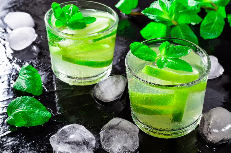 Summer drink Mojito, with lime, mint and ice cubes, on a black background with water drops stock images
