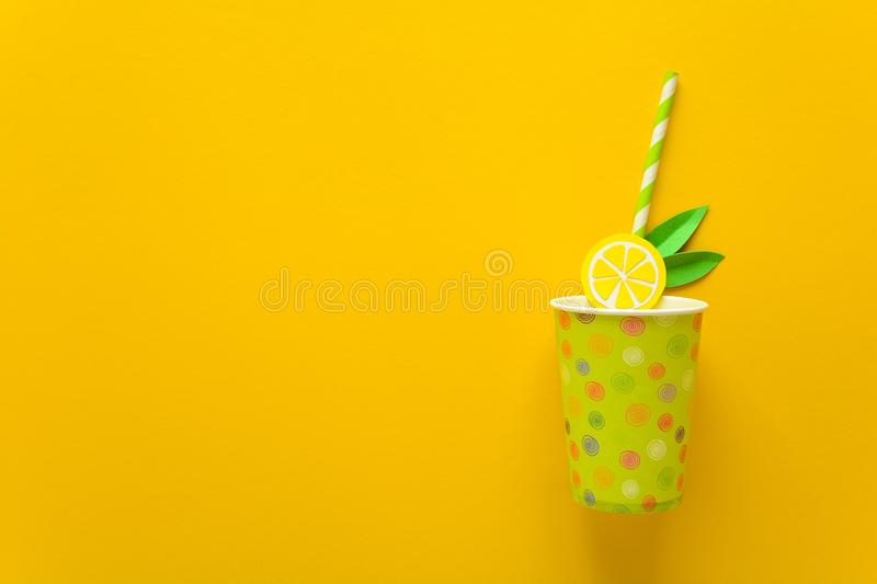 Summer drink with paper cut lemon slices and leaves on yellow paper background. Summer drink concept. Top view. Flat lay royalty free stock photography