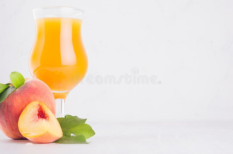 Summer drink - peach juice with whole peach, green leaf and slice on white light soft wood board, copy space. royalty free stock photo
