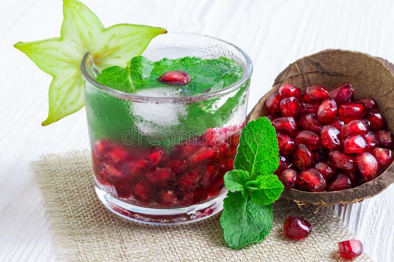 Summer drink with pomegranate, fresh mint and slice of carambola on a white wooden background royalty free stock photos
