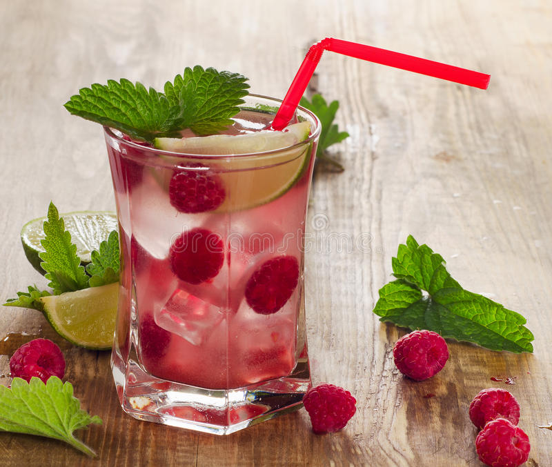 Summer drink with raspberries, lime and ice on old wooden table. Selective focus royalty free stock photos