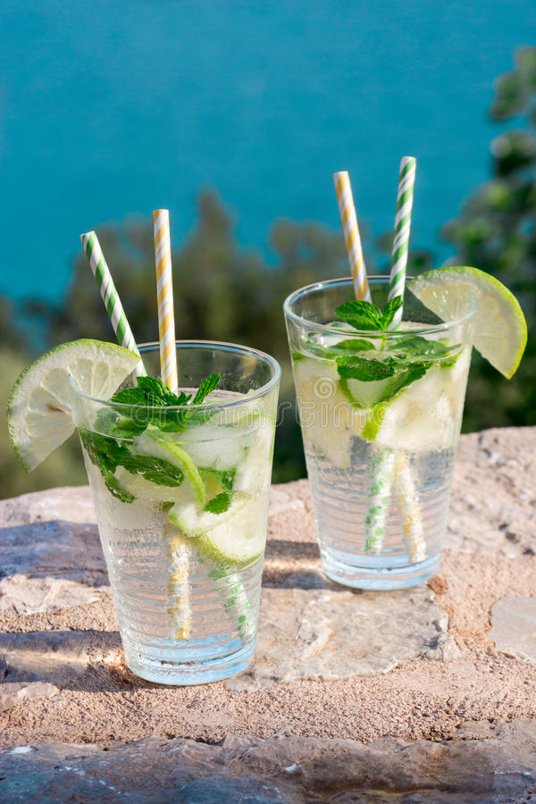 Summer drink soda water cocktail. Two glasses with soda water, lemon slices, mint leaves and ice cubes on the background of sea. Summer drink soda water royalty free stock photography