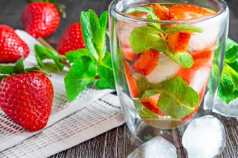 Summer drink of strawberries and mint with ice cubes on dark wooden table royalty free stock photos
