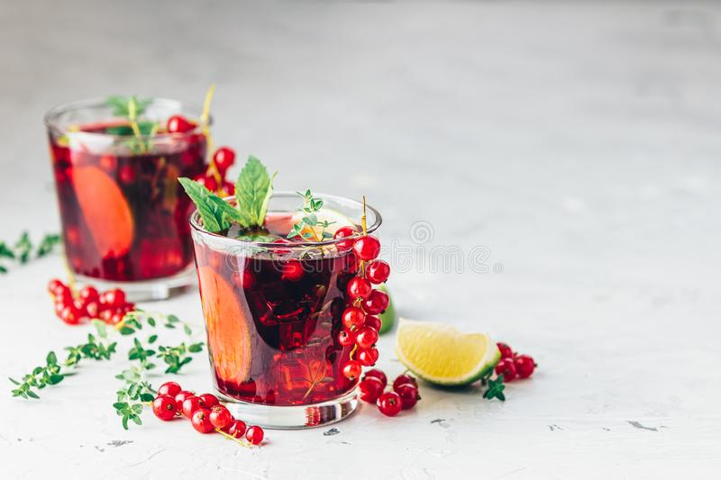 Summer drinks and alcoholic cocktails Currant mojito. Cold red cocktail with currant, lime, mint, thyme and ice in glass on light gray concrete surface table royalty free stock photography