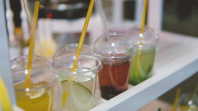 Summer drinks in plastic. Refreshing summer drinks with a straw and fruit. Shallow focus royalty free stock image