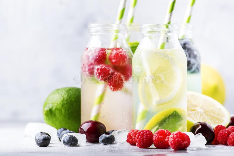 Summer drinks set. Berry, fruit and citrus non-alcoholic refreshing ice cold beverages and cocktails in glass bottles on white. Background stock images