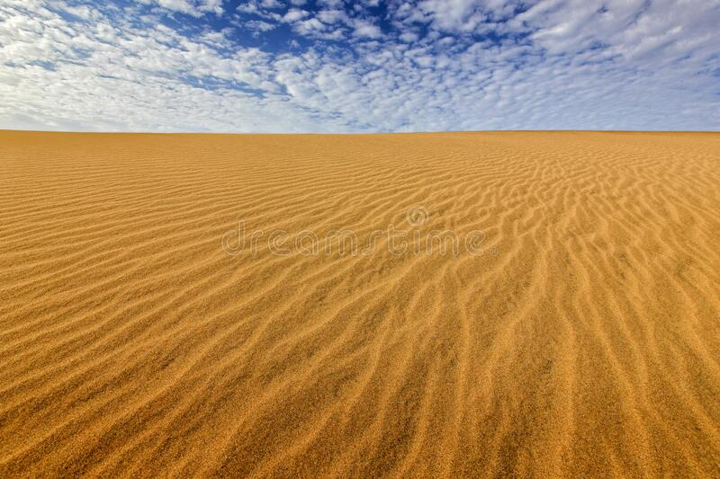 Summer dry landscape in Africa. Black pebble stones. Sandy waves in the wild nature. Dunas Maspalomas, Gran Canaria, Spain. Beautiful rare blue sky with white royalty free stock images