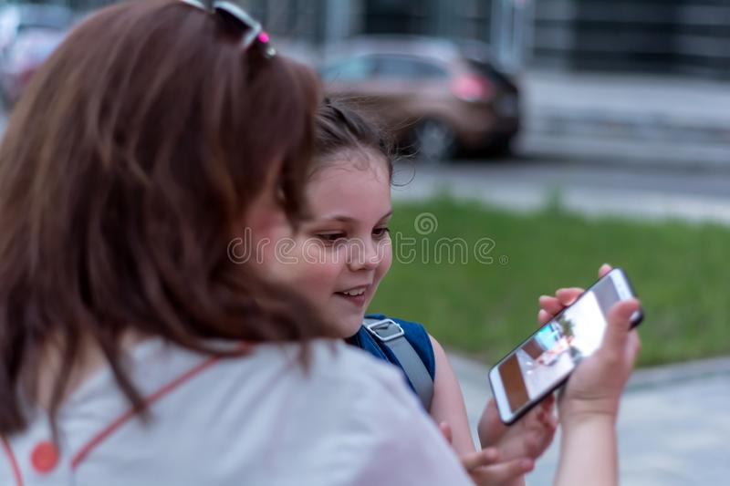 Summer evening. Holidays. Mother and daughter watch nice photo on smartphone stock photography