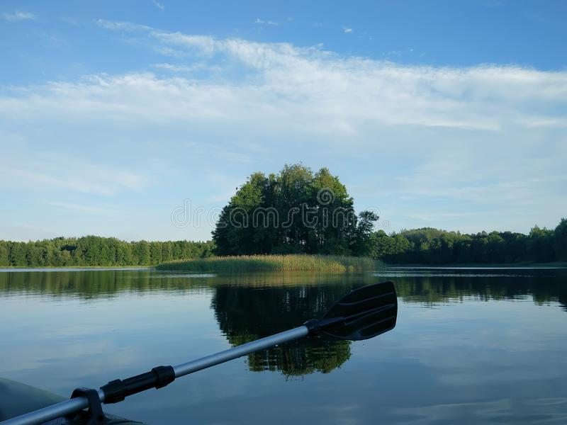 Landscape with lake surface and fragment of paddle of inflatable boat. stock image