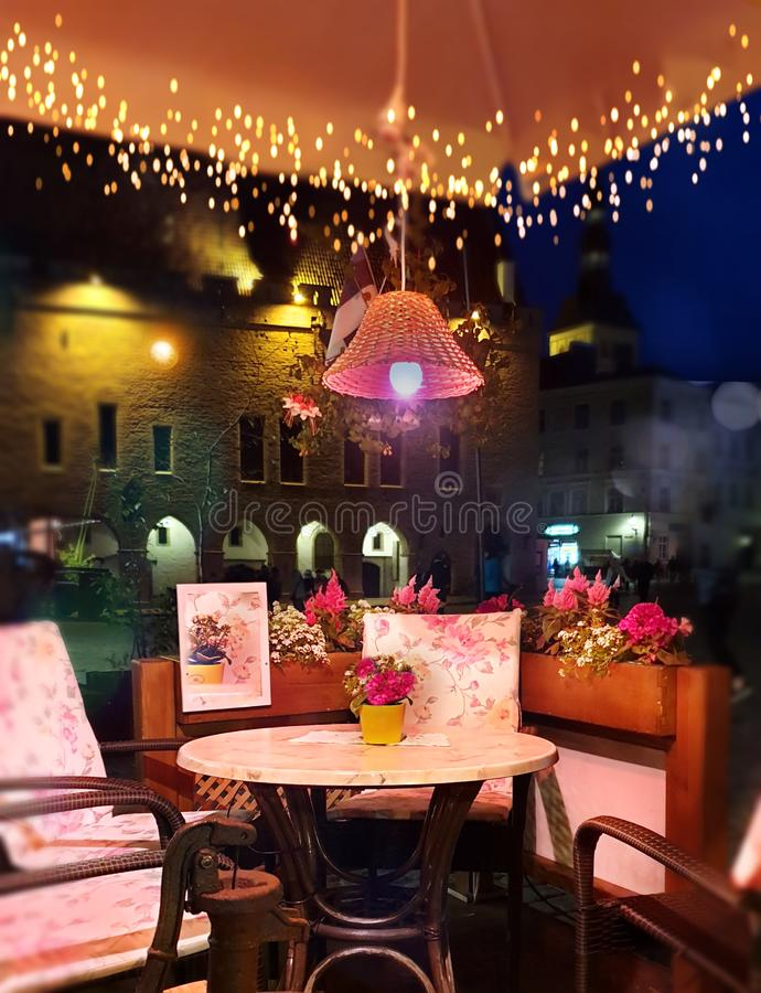 Summer Evening Lighting illumination Street Cafe decoration Table with flowers on top And Lamp Restaurant outdoor in the city rela stock photo