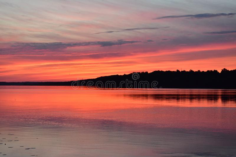 Summer evening red sunset over the river clouds and water surface royalty free stock image
