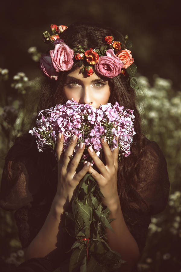 Summer fairy. Young beautiful woman portrait with flowers in field summer day retro colors stock image