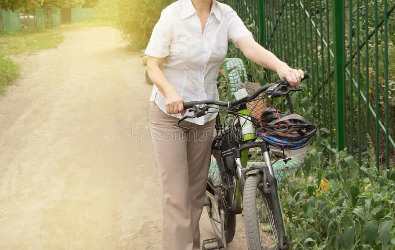 Summer, family, happy young woman on a Bicycle standing on the road near the fence of the Park royalty free stock photos