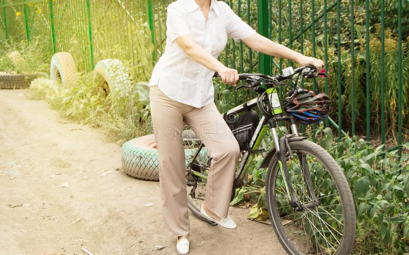Summer, family, happy young woman on a Bicycle standing on the road near the fence of the Park. Bike active girl pedal wheel pants fitness travel nature forest stock images