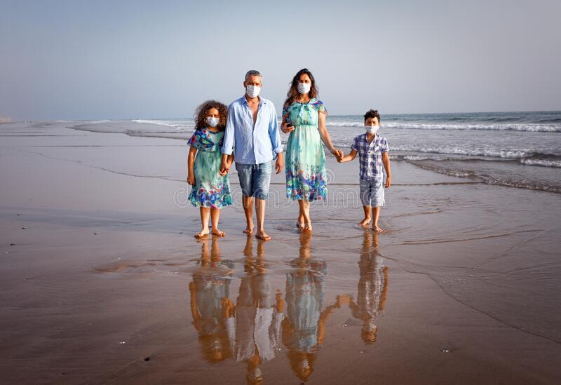 Summer holidays during a pandemic covid-19. A family of  4 people, mother, father, son and daughter walk along the shore in protective masks. Summer 2020 Agadir