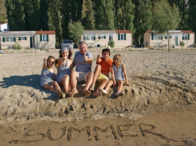 Summer family thumbs up. Smiling family (father with mother an d children in navy clothes) thumbs up on sandy beach at Adriatic sea (Croatia). In sandy beach stock photo