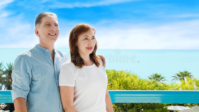 Summer family vacation. Happy middle aged couple having fun on travel holidays weekend. Sea and beach background. Copy space. Selective focus royalty free stock photo