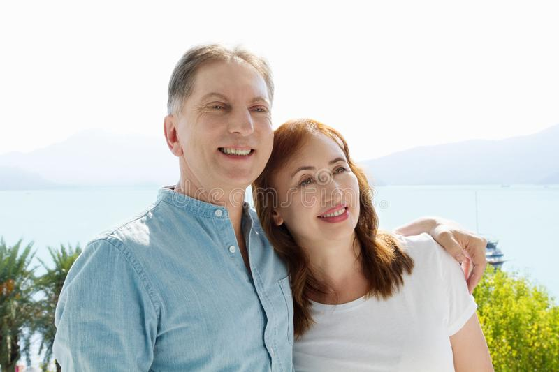 Summer family vacation. Happy middle aged couple having fun on travel holidays weekend. Sea and beach background. Copy space.  royalty free stock image