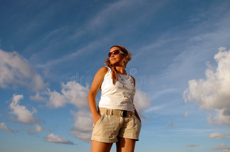 Summer fashion. Young girl wearing sunglasses against blue sky stock image