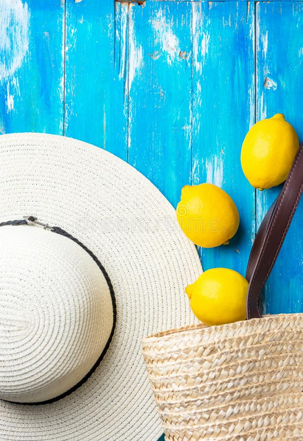 Summer fashion background. Straw hat wicker handwoven beach bag fresh lemons on blue wood. Travel vacation concept. Provence style. Poster banner with copy stock photography