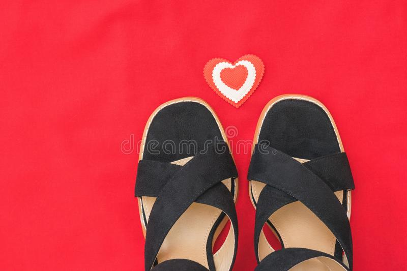 Summer fashion black women`s shoes on red fabric with red heart. Flat lay. The view from the top stock image
