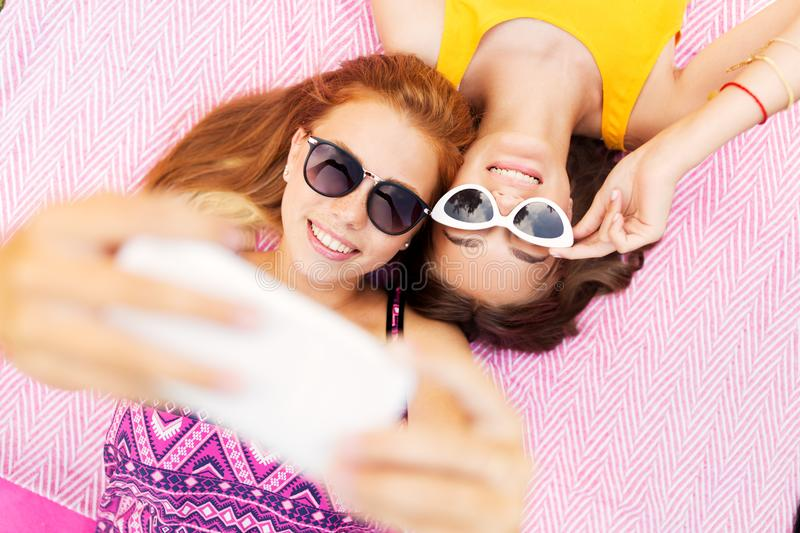 Teenage girls in sunglasses taking selfie. Summer fashion, eyewear and leisure concept - smiling teenage girls in sunglasses lying on picnic blanket taking royalty free stock images