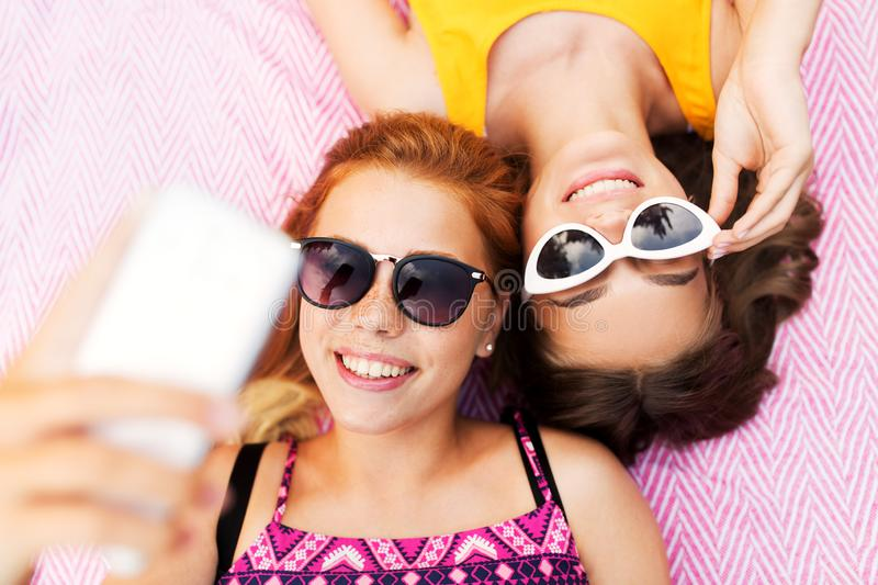 Teenage girls in sunglasses taking selfie. Summer fashion, eyewear and leisure concept - smiling teenage girls in sunglasses lying on picnic blanket taking royalty free stock photography