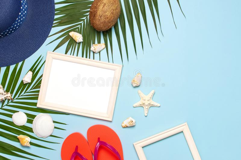 Summer fashion flat lay. Blue hat coral flip flops tropical palm leaves sunscreen white photo frame coconut seashells starfish on royalty free stock image