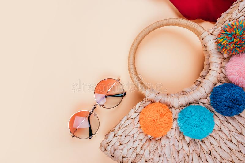 Summer fashion flatay. Summer fashion flatlay with gradient round sunglasses, trendy straw bag with pompoms and red swimsuit on the beige background. Perfect royalty free stock photos