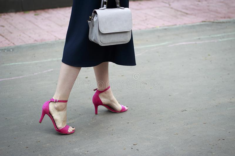 Summer fashion outfit. Girl in dress and stylish pink sandals walks down the street royalty free stock images