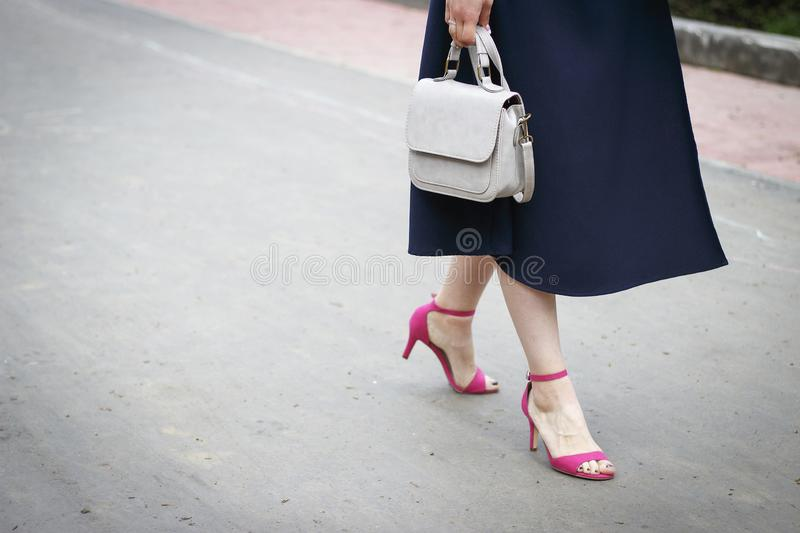 Summer fashion outfit. Girl in dress and stylish pink sandals walks down the street stock photography