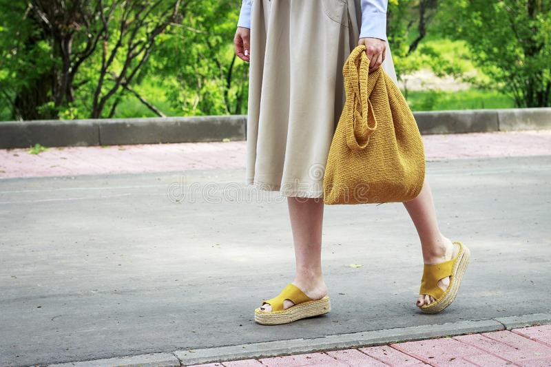 Summer fashion outfit. Girl in dress, yellow shoes and trendy knitted bag, side view royalty free stock images