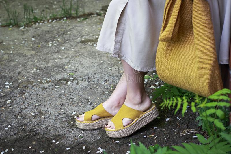 Summer fashion outfit. Girl in dress, yellow shoes and trendy knitted bag, side view royalty free stock photography