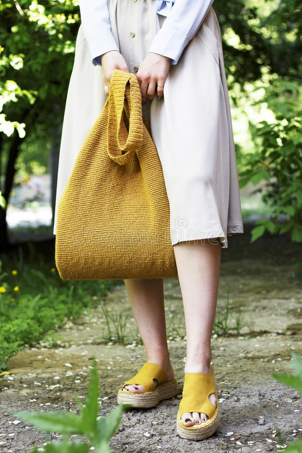 Summer fashion outfit. Girl in dress, yellow shoes and trendy knitted bag, top view royalty free stock photo