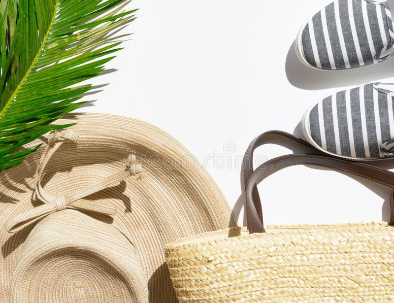 Summer fashion tropical vacation concept. Women`s female beachwear straw hat wicker shoulder bag green palm leaves on white stone royalty free stock photos