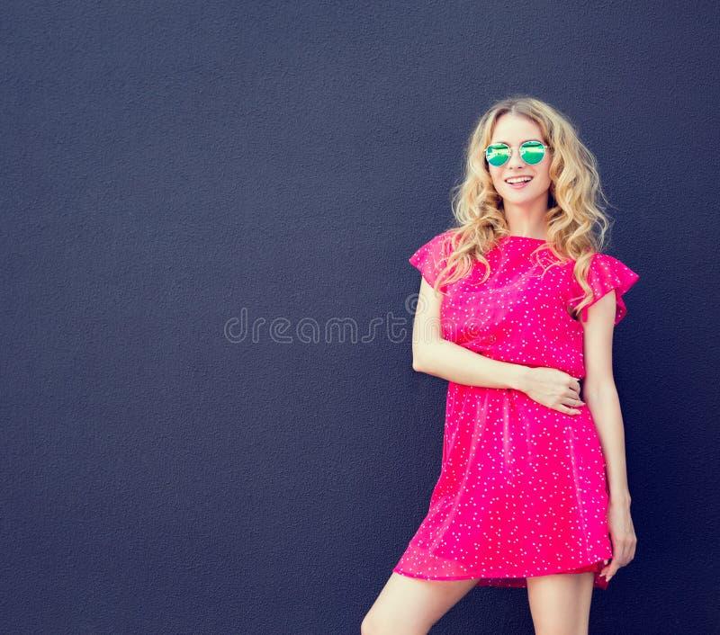Summer Fashion Woman in Pink Dress at Dark Wall royalty free stock photos