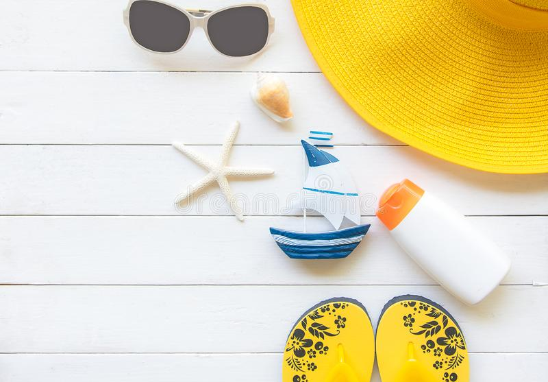 Summer Fashion woman yellow big hat and accessories in the beach. Tropical sea.Unusual top view, wood white background. Summer Concept stock images