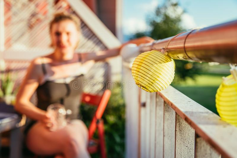 Summer feeling on the balcony: Close up of lampions, smiling girl in the blurry background. Close up of summer lampions on a balcony, girl in the blurry stock image