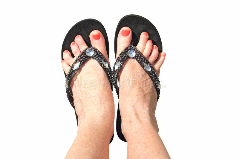 Summer feet isolated. Womans feet with nail polish and wearing flip-flops/thongs isolated using clipping path royalty free stock photography