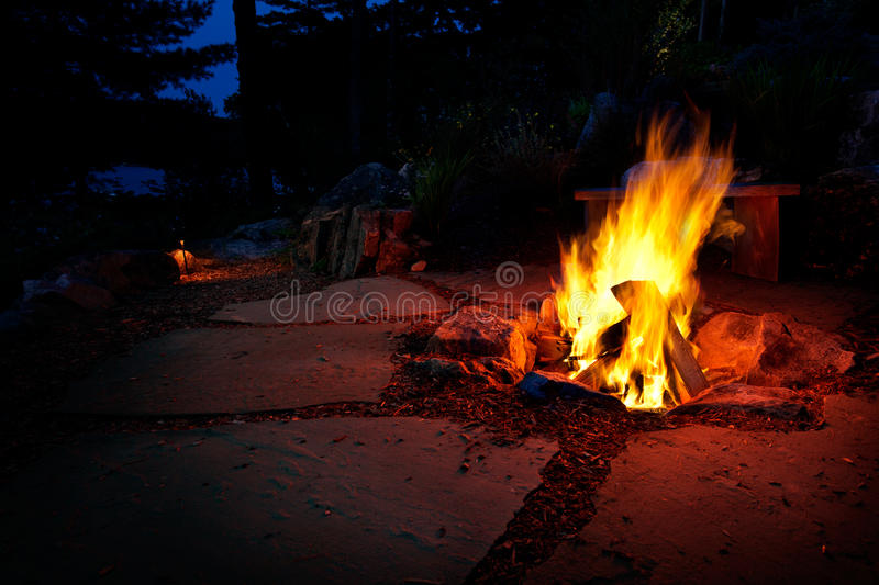 Summer fire pit. Warm glow of an outside fire pit on a summer evening royalty free stock photography