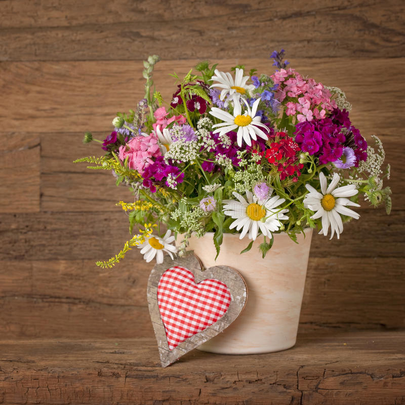 Summer flowers in vase. On wooden background royalty free stock images
