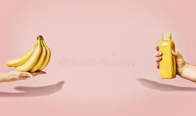 Summer food and beverages background with bananas and yellow drink bottle in female hand at pastel pink. Background, front view, banner or template stock images