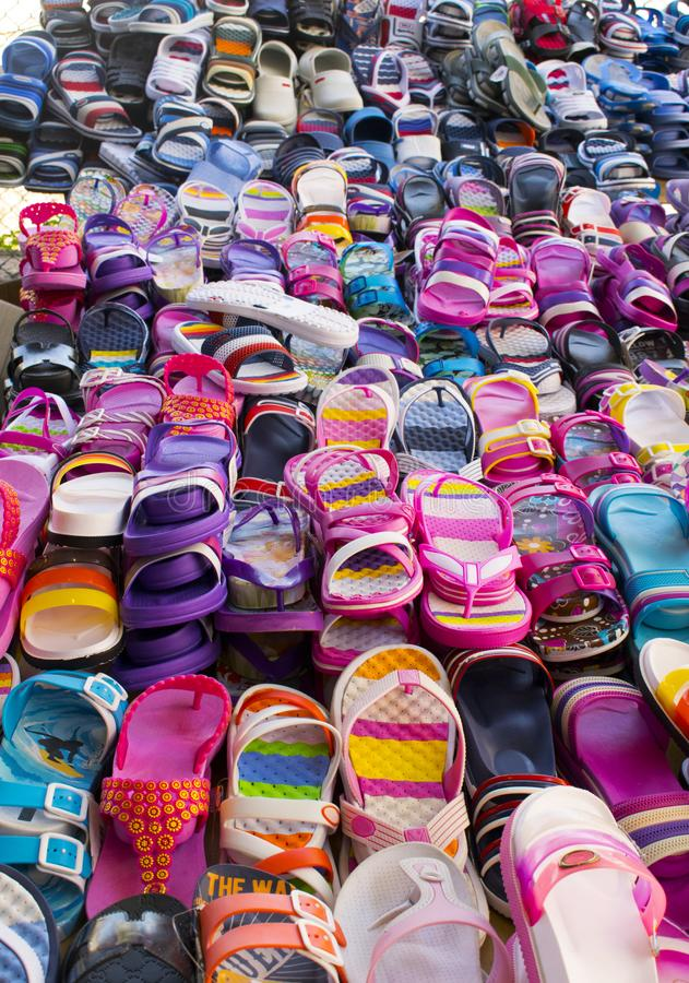 Summer footwear. Flip-flops and sandals on the market. royalty free stock photos