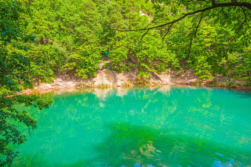 Summer forest lake emerald color effect. The Blue Lake from Romania change its color depending the light: from blue to emerald green. It resulted from the stock photos