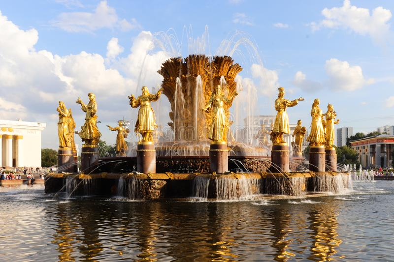Summer fountain with gold sculptures. Blue sky with white clouds. royalty free stock photography
